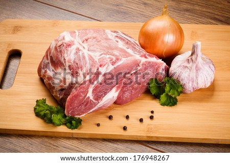 Fresh raw pork chops on white cutting board  - stock photo