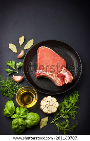 Fresh raw pork chops with spices and herbs on black background, top view - stock photo