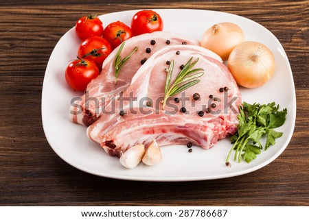 fresh raw pork loin with bay leaf on wooden board  - stock photo