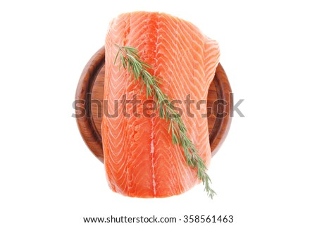 fresh raw red fish fillet on wooden plate and rosemary - stock photo