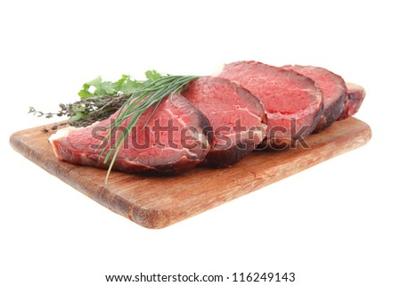 fresh raw red meat with thyme and chives on wooden plate isolated on white background - stock photo