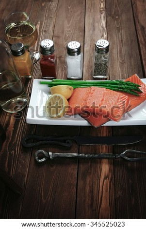 fresh raw salmon fillet served with lemon and white wine in wineglass, wooden barrel, bottle, on white plate over vintage wood table with handmade cutlery knife and fork - stock photo