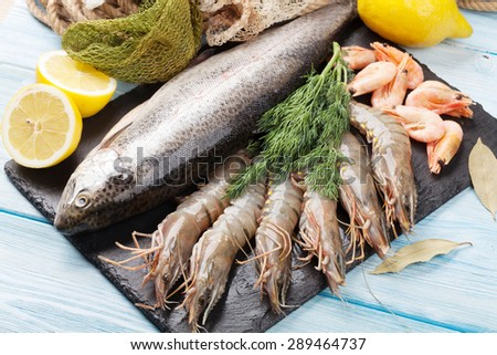 Fresh raw sea food with spices on stone plate over wooden table background. Top view - stock photo