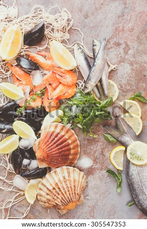 Fresh raw sea food with spices. Overhead shot of raw scallops, fish, shrimps and mussels with lemon and spices  on crushed ice. Preparing food concept - stock photo