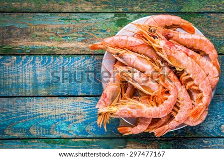 fresh raw shrimps in a bowl on a wooden table - stock photo