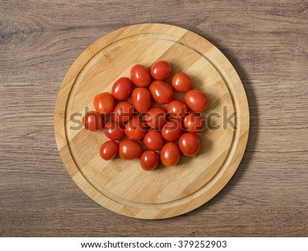 Fresh raw tomatos food. Red cherry tomatoes on the bamboo cutting board. Brown wood imitating background - stock photo