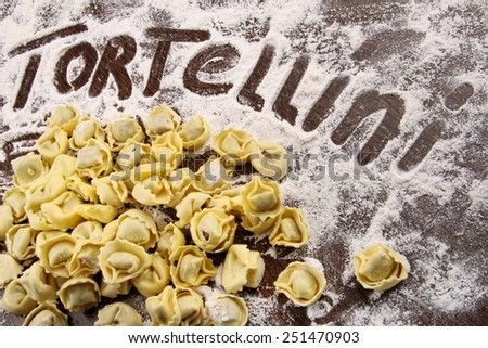 Fresh, raw tortellini with flour on wooden table - stock photo