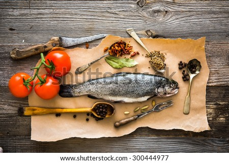 fresh raw trout with tomatoes and spices on a wooden background  - stock photo