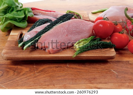 fresh raw turkey meat steak fillet with vegetables kale tomatoes lettuce red hot chili pepper and dark olives on cutting board over wooden table - stock photo
