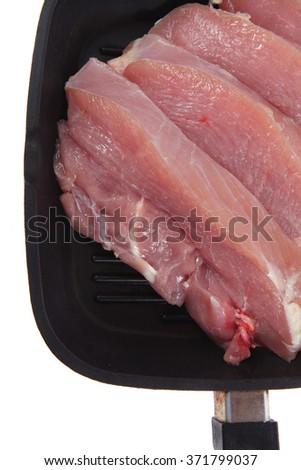 fresh raw turkey pieces on black pan isolated over white background - stock photo