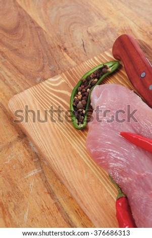 fresh raw turkey steak fillet with red hot chili pepper and green salad on cutting board over wooden table - stock photo
