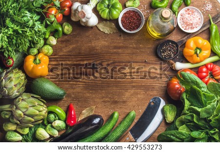 Fresh raw vegetable ingredients for healthy cooking or salad making on rustic wood background, top view, copy space. Diet or vegetarian food concept - stock photo