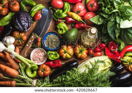 Fresh raw vegetable ingredients for healthy cooking or salad making, top view. Olive oil in bottle, spices and knife. Diet or vegetarian food concept - stock photo