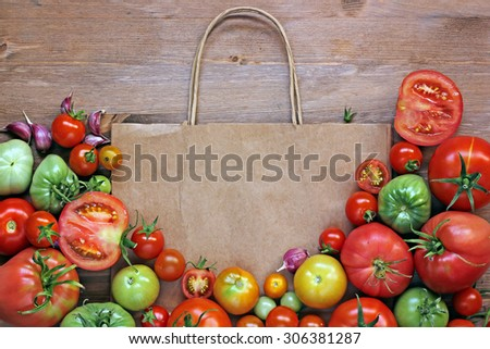 Fresh red and green tomatoes on a table lie on a paper package, the top view. Tomatoes mature and immature. Paper package. A place for your text. - stock photo