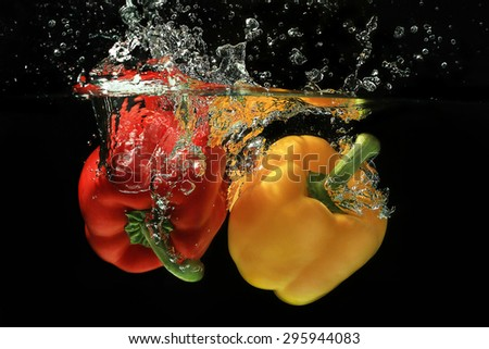 Fresh red and yellow bell pepper gets hit by a water stream on black background. Water splashes concept  - stock photo