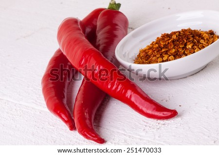 Fresh red and yellow chili peppers with a small bowl of dried cayenne pepper spice for use as a pungent hot seasoning and flavoring in cooking - stock photo