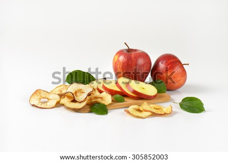 fresh red apples and apple rings on wooden cutting board - stock photo