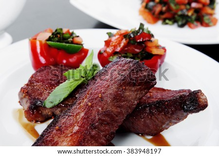 fresh red beef meat steak barbecue garnished vegetable salad and basil on white plate over black wooden table with bbq sauce in sauceboat - stock photo