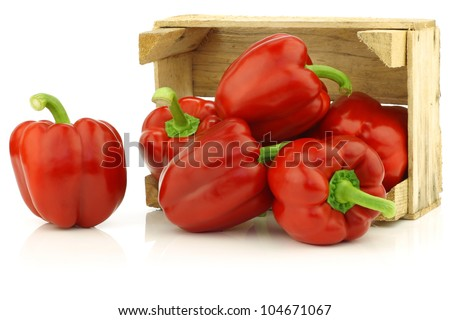 fresh red bell peppers (capsicum) in a wooden crate on a white background - stock photo