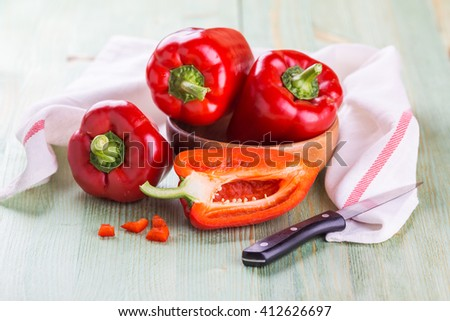 Fresh red bell peppers on a bright wooden background - stock photo