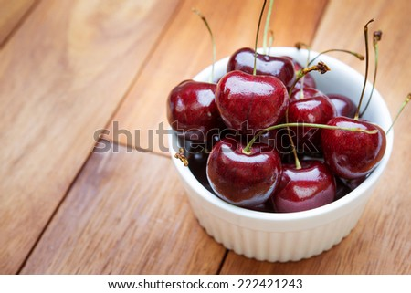 fresh red cherries in white cup on a wooden table background - stock photo
