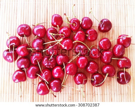Fresh red cherries on wood plate - stock photo