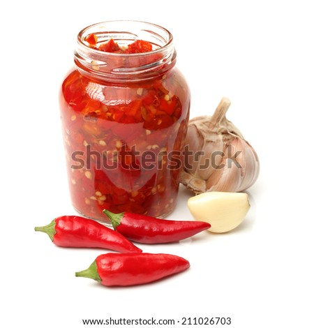 Fresh red chilly and bottled chili sauce over white background - stock photo