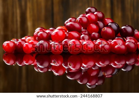 Fresh red cranberries on wooden background. Selective focus - stock photo