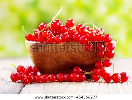fresh red currant in bowl on wooden table, over green background - stock photo