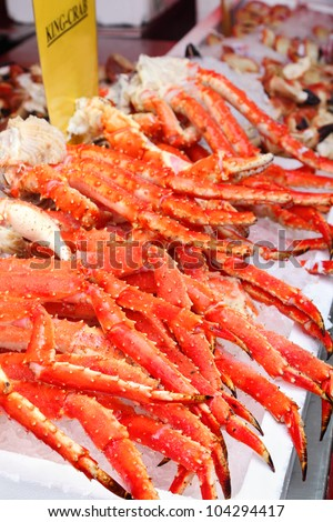 Fresh red king-crab legs in ice at seafood market; cabs high content protein and low calorie - stock photo