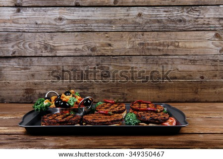 fresh red meat beef hamburger served on black tray with vegetables olives hot chili pepper tomatoes mushrooms over wooden table with empty space for text on background - stock photo