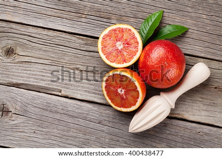 Fresh red oranges and juicer on wooden table. Top view with copy space - stock photo