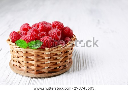 Fresh red raspberries in wicker basket on wooden background - stock photo