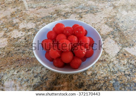 Fresh red, ripe, juicy, summertime, watermelon balls. Presented on white plate with neutral granite background. - stock photo