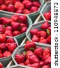 Fresh red strawberries packed in boxes for sale on a market - stock photo