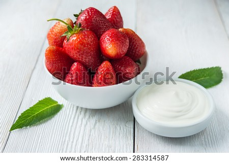 Fresh red strawberries with cream om white wood table. Easy dietary breakfast. - stock photo