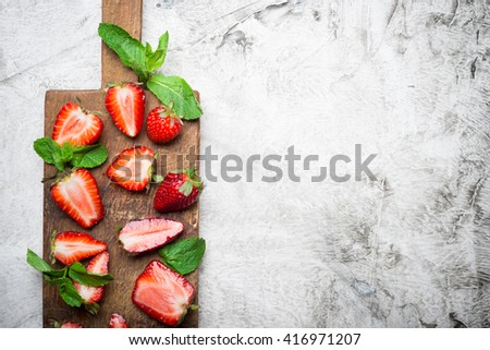 Fresh red strawberry with fresh mint on a wooden cutting board - stock photo