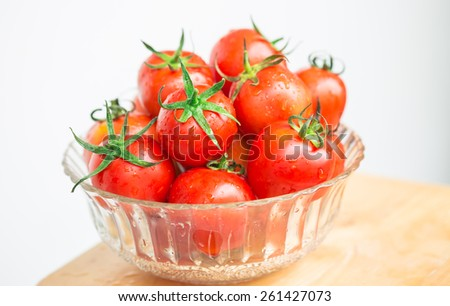 Fresh red tomato in glass bowl - stock photo