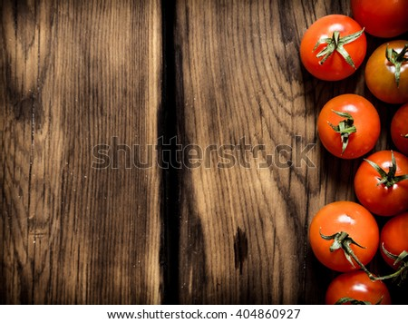 Fresh red tomatoes . On a wooden background. - stock photo