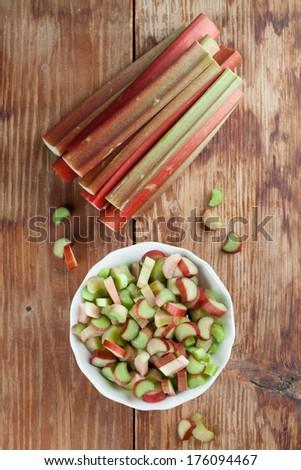 Fresh rhubarb on wooden background. Shallow dof - stock photo