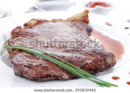 fresh rich juicy grilled beef meat steak fillet on white plate over wooden table decorated with sauces and cutlery new york style - stock photo