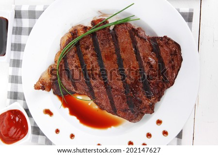 fresh rich juicy grilled beef meat steak fillet with marks on white plate over wooden table decorated with sauces and cutlery new york style - stock photo