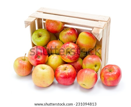 Fresh ripe apples spreading out from wooden crate - stock photo