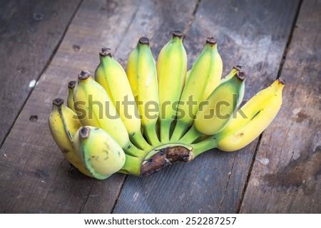 Fresh ripe bananas on wooden background - stock photo