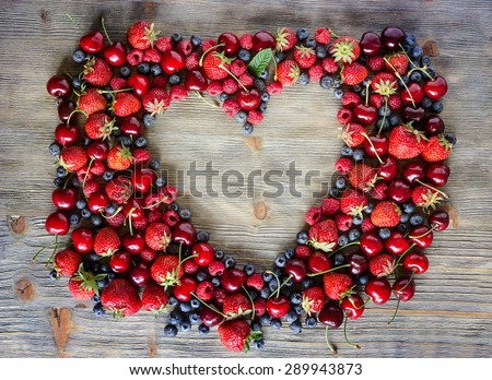 Fresh ripe berries, cherries, raspberries, blueberries copy space background, summer fruits, harvest concept, vitamins food, heart shaped - stock photo