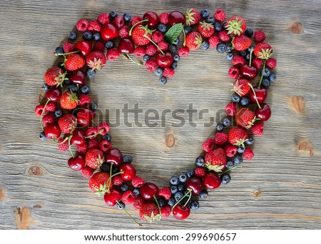 Fresh ripe berries, cherries, raspberries, blueberries lots of copy space, wooden background, summer fruits, harvest concept, vitamins food, heart shaped - stock photo