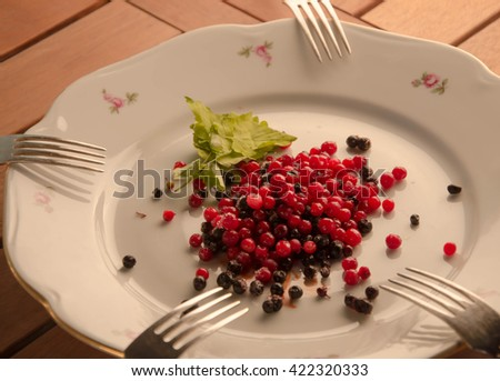 Fresh ripe berries plate on wooden table background - stock photo