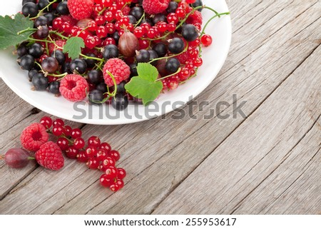 Fresh ripe berries plate on wooden table background with copy space - stock photo