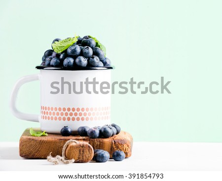 Fresh ripe blueberries in country style enamel mug on rustic wooden board over mint pastel background, selective focus - stock photo