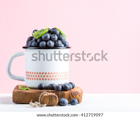 Fresh ripe blueberries in country style enamel mug on rustic wooden board over pastel pink background, selective focus - stock photo